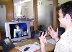 Normal_deaf_or_hoh_person_at_his_workplace_using_a_video_relay_service_to_communicate_with_a_hearing_person_via_a_video_interpreter_and_sign_language_svcc_2007_brigitte_sli___mark